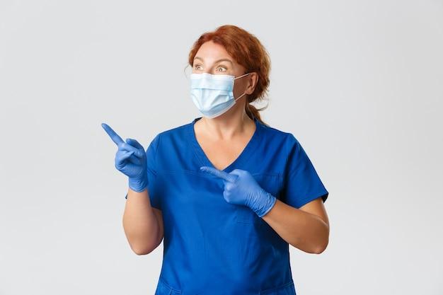 Operatori sanitari, pandemia covid-19, concetto di coronavirus. dottoressa impressionata ed eccitata, infermiera in maschera, guanti e scrub guardando e indicando l'angolo in alto a sinistra con espressione stupita.
