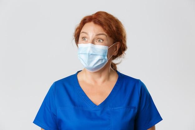 Operatori sanitari, pandemia covid-19, concetto di coronavirus. medico femminile impressionato ed eccitato, infermiera in maschera, guanti e scrub guardando nell'angolo in alto a sinistra con espressione stupita.