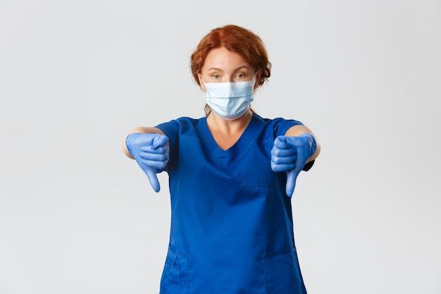 Operatori sanitari, pandemia covid-19, concetto di coronavirus. dottoressa professionista dispiaciuta seria, infermiera in scrub, maschera facciale e guanti che puntano il dito verso il basso in segno di disapprovazione, non lo consiglio.