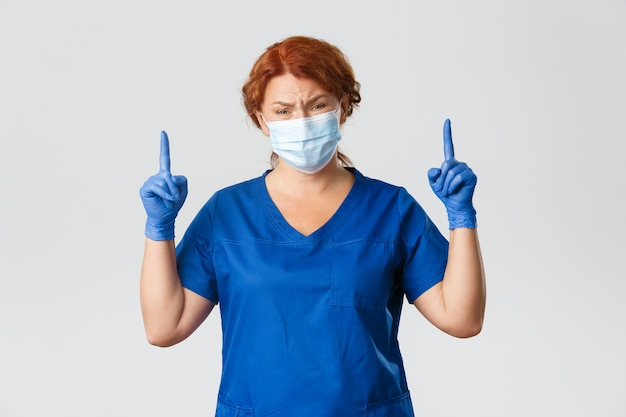 Operatori sanitari, pandemia covid-19, concetto di coronavirus. dottoressa rossa scettica e disinteressata, medico che guarda con giudizio, punta il dito verso qualcosa di insignificante, indossa una maschera.