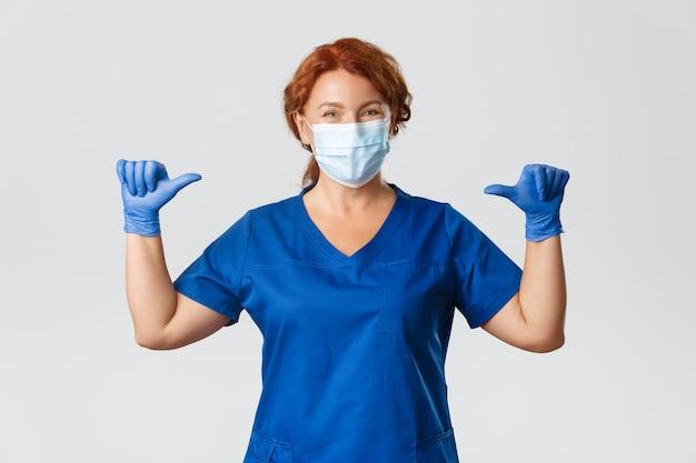 Operatori sanitari, pandemia covid-19, concetto di coronavirus. sorridente infermiera piacevole, medico professionista femminile in maschera medica, guanti e scrub che punta a se stessa, essendo un vero professionista, sfondo grigio.