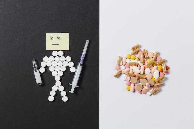 Compresse rotonde colorate di farmaci disposte in astratto su sfondo nero bianco