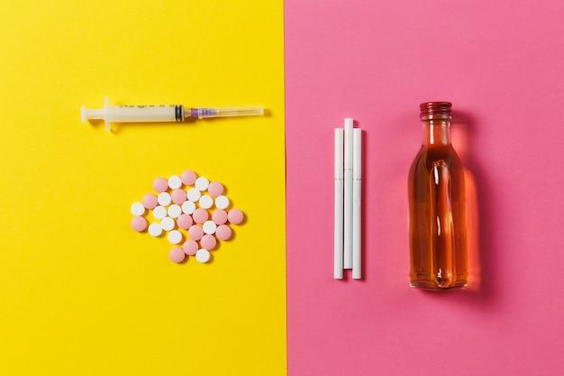 Le pillole rotonde variopinte delle compresse del farmaco hanno organizzato l'alcool astratto e vuoto della bottiglia dell'ago della siringa, sigarette sul fondo della rosa gialla. scelta del trattamento stile di vita sano. copia spazio pubblicitario.