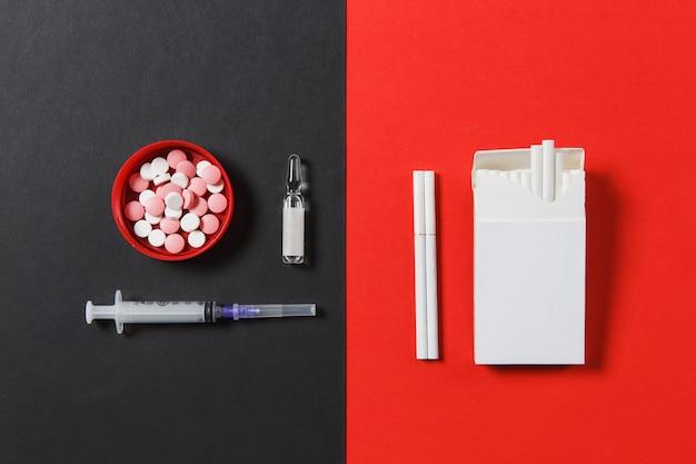 Pillole di compresse rotonde colorate di farmaci, ago per siringa vuoto, fiala, pacchetto di sigarette