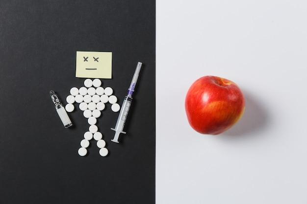 Compresse rotonde di farmaci disposte umane tristi su sfondo nero bianco. mela rossa, fiala, ago della siringa vuoto, design delle pillole. trattamento, scelta, concetto di stile di vita sano. copia spazio pubblicitario.
