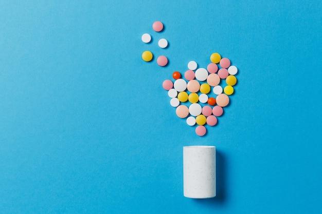 Compresse rotonde bianche e colorate di farmaci a forma di cuore isolato su sfondo blu. pillole di forma geometrica, bottiglia. concetto di salute, trattamento, scelta, stile di vita sano. copia spazio pubblicitario.