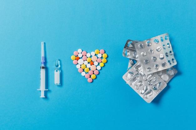 Compresse rotonde bianche e colorate di farmaci a forma di cuore isolato su sfondo blu. pillole, imballaggi, ago della siringa vuoto. concetto di trattamento, scelta, stile di vita sano. copia spazio pubblicitario.