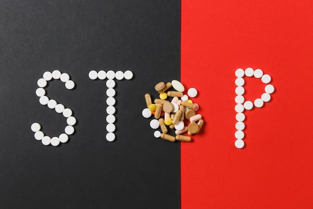 Compresse rotonde bianche e colorate di farmaci in parola stop isolato su sfondo rosso nero. forma di pillole, lettera. concetto di salute, trattamento, scelta di uno stile di vita sano. copia spazio pubblicitario.