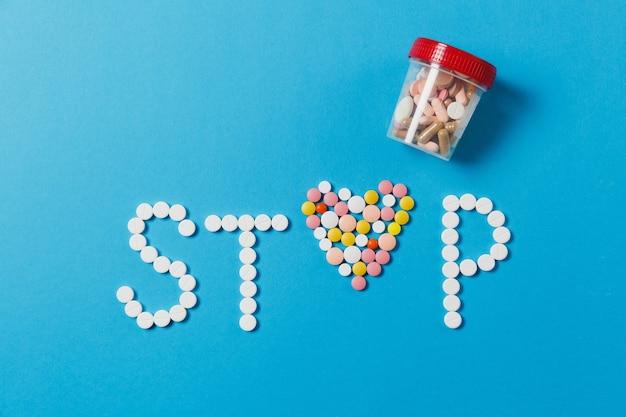 Compresse rotonde bianche e colorate di farmaci in parola stop isolato su sfondo blu. pillole a forma di cuore, lettera del barattolo di analisi. concetto di stile di vita sano scelta di trattamento sanitario. per la pubblicità.