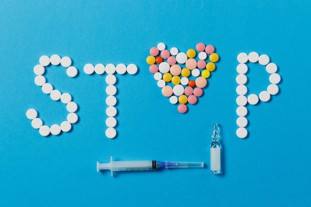 Compresse rotonde bianche e colorate di farmaci in parola stop isolato su sfondo blu