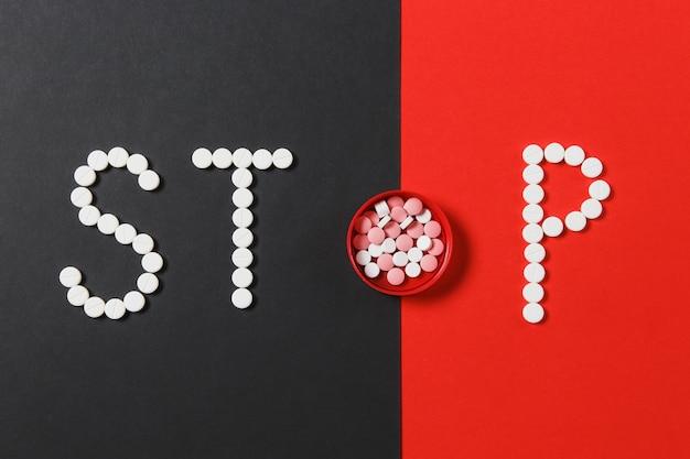 Compresse rotonde bianche e colorate di farmaci in parola stop isolato