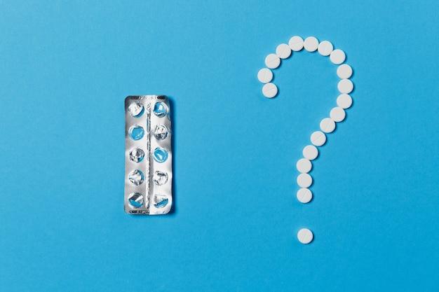 Compresse rotonde bianche per farmaci disposte a forma di punto interrogativo isolate su sfondo di colore blu