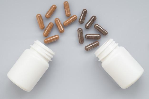 La capsula medicinale fuoriesce da due bottiglie di plastica su una superficie leggera