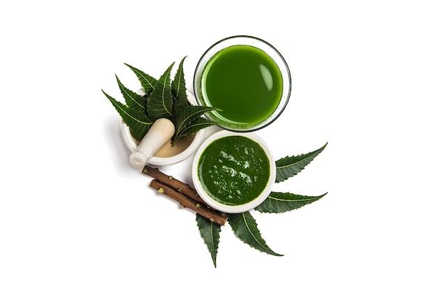 Foglie di neem medicinali in mortaio e pestello con pasta di neem, succo e ramoscelli su priorità bassa bianca