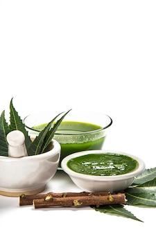 Foglie di neem medicinali in mortaio e pestello con pasta di neem, succo e ramoscelli sulla superficie bianca