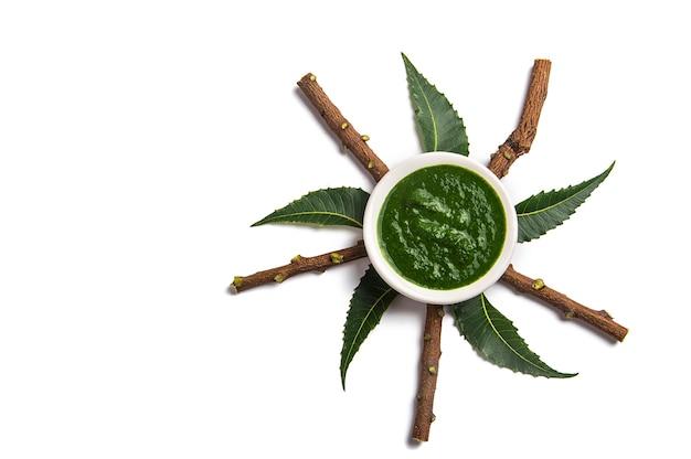 Foglie di neem medicinali con pasta nella ciotola e ramoscelli sulla superficie bianca
