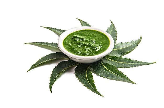 Foglie di neem medicinali con pasta nella ciotola su priorità bassa bianca.
