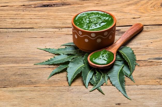 Foglie di neem medicinali con pasta su legno