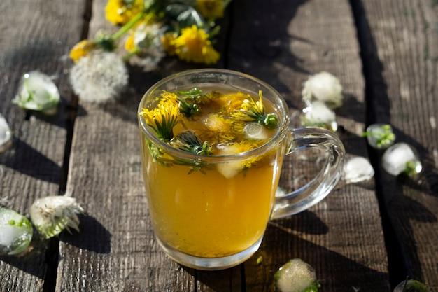 Tè medicinale dal dente di leone in tazza di vetro e fiore di tarassaco sulla tavola rustica in legno con ghiaccio
