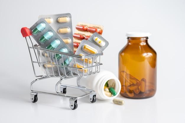 Consegna della medicina in carrello e bottiglia della droga su bianco