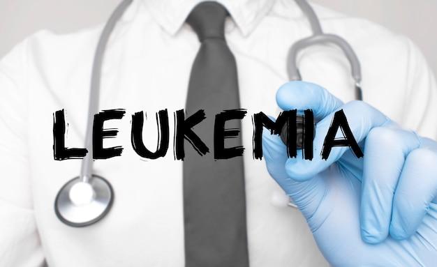 Concetto di medicina. il dottore scrive la parola leucemia. immagine di una mano che tiene un pennarello isolato su uno sfondo bianco.