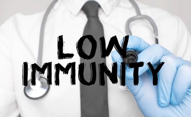 Concetto di medicina. il dottore scrive la parola immunità bassa. immagine di una mano che tiene un pennarello isolato su uno sfondo bianco.