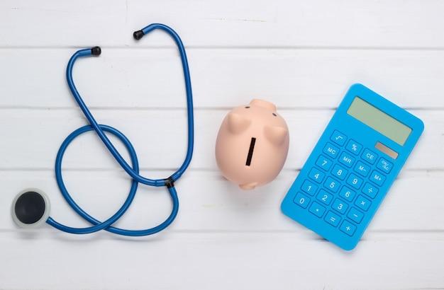 Concetto di medicina. budget medico. stetoscopio con salvadanaio, calcolatrice su superficie di legno bianca. vista dall'alto. lay piatto
