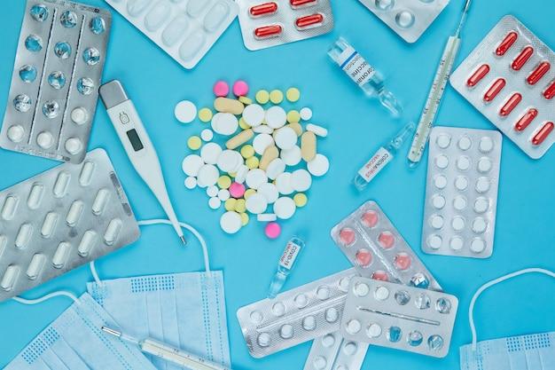 Medicina per coronavirus. medicinali nella lotta contro covid-19. pillole, siringhe, termometro, maschera medica su un tavolo blu. .