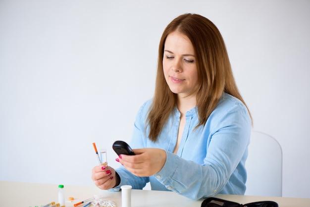 Medicina, diabete, glicemia, assistenza sanitaria e concetto di persone - chiuda in su della donna che controlla il livello di zucchero nel sangue dal glucometro a casa