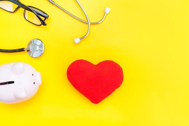 Stetoscopio dell'attrezzatura del medico di medicina o cuore rosso dei vetri del porcellino salvadanaio del fonendoscopio isolato sul giallo alla moda