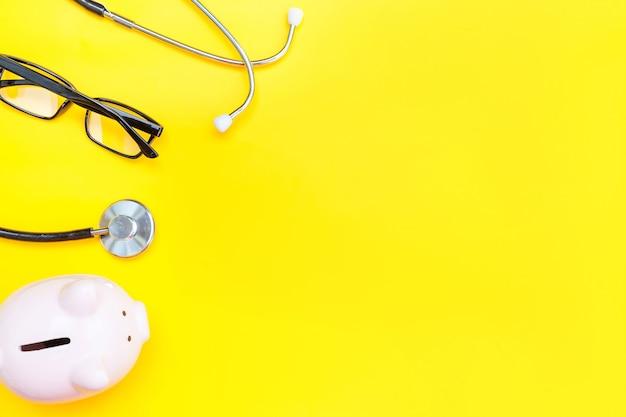Vetri della banca piggy dello stetoscopio dell'attrezzatura del medico di medicina isolati sulla tabella gialla