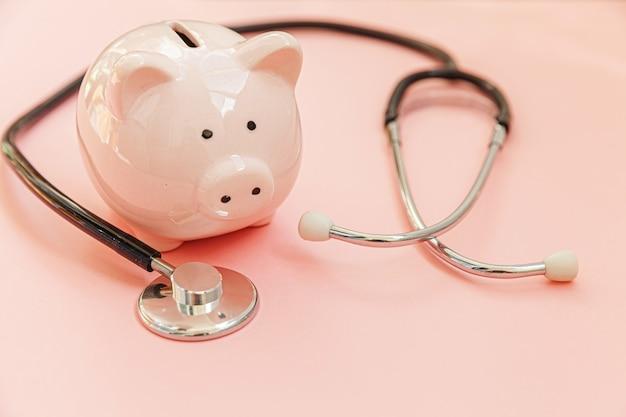 Stetoscopio e porcellino salvadanaio dell'attrezzatura di medico della medicina isolati su fondo pastello rosa. controllo finanziario o risparmio di sanità per il concetto di costi di assicurazione medica. copia spazio.