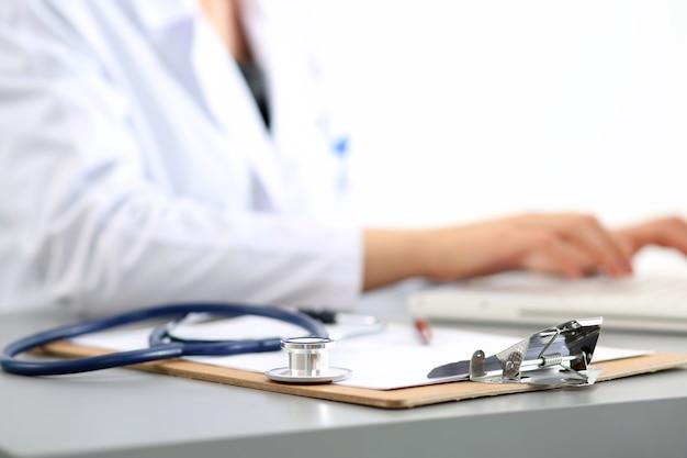 Luogo di lavoro del medico di medicina. concentrarsi sullo stetoscopio, le mani del medico digitando qualcosa. sanità e concetto medico. copyspace