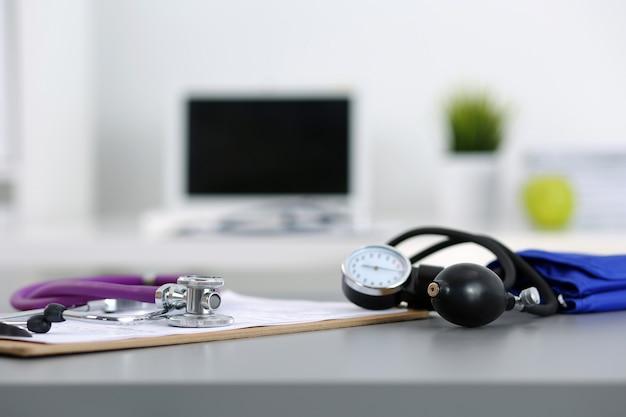 Luogo di lavoro del medico di medicina. stetoscopio e manometro sdraiato sul tavolo presso l'ufficio del medico. sanità e concetto medico
