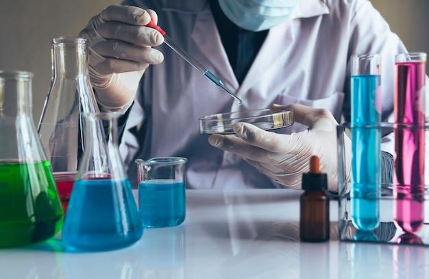 Medico di medicina con la siringa in mano e bottiglie di vetro colorate