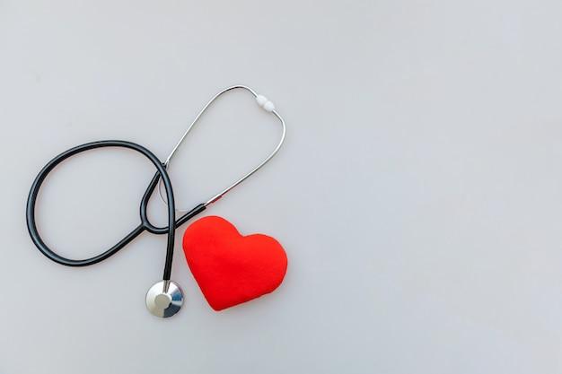 Stetoscopio dell'attrezzatura della medicina e cuore rosso isolato su fondo bianco