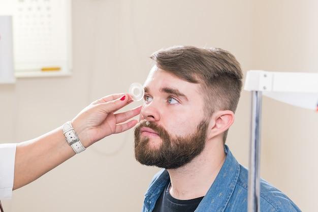 Medicina, salute, concetto di oftalmologia - l'oftalmologo esamina gli occhi del paziente.