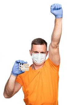 Medicina e concetto di assistenza sanitaria. giovane in maschera e guanti protettivi blu che tengono pillole su sfondo bianco