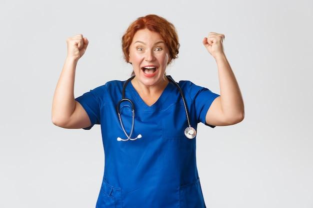 Concetto di medicina, sanità e coronavirus. operatore medico eccitato ed elettrizzato che si rallegra di un evento di successo, pompa il pugno e dice evviva, gesto di sì, vincendo o celebrando una buona notizia.