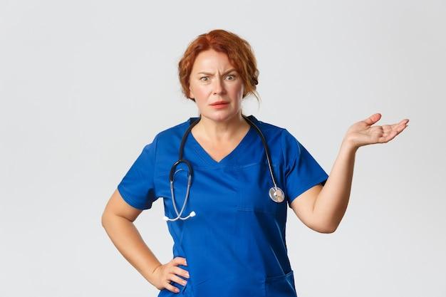 Concetto di medicina, sanità e coronavirus. l'operaio medico donna rossa frustrata e infastidita, medico che sembra confuso e arrabbiato, alza la mano di lato con sgomento, che cos'è questo gesto.