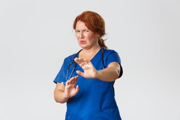 Concetto di medicina, sanità e coronavirus. redhead riluttante e disgustata dottoressa, infermiera che chiede di stare alla larga, allunga le mani in segno di rifiuto e fa smorfie, rabbrividisce per l'avversione, muro grigio.