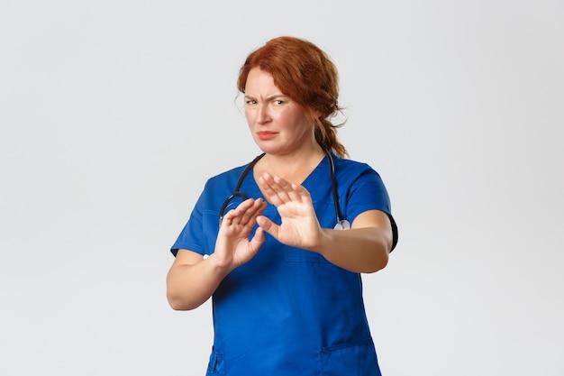 Concetto di medicina, sanità e coronavirus. dottoressa rossa riluttante e scontenta, infermiera che chiede di stare lontano, allunga le mani in segno di rifiuto e fa smorfie, rabbrividisce per l'avversione, sfondo grigio.