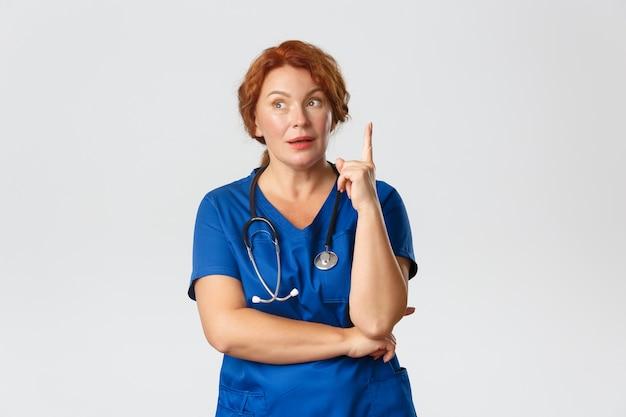 Concetto di medicina, sanità e coronavirus. premurosa infermiera rossa di mezza età, dottore in camice ha supposizioni o suggerimenti, alza il dito, ha un'idea, condivide il suo pensiero, muro grigio.
