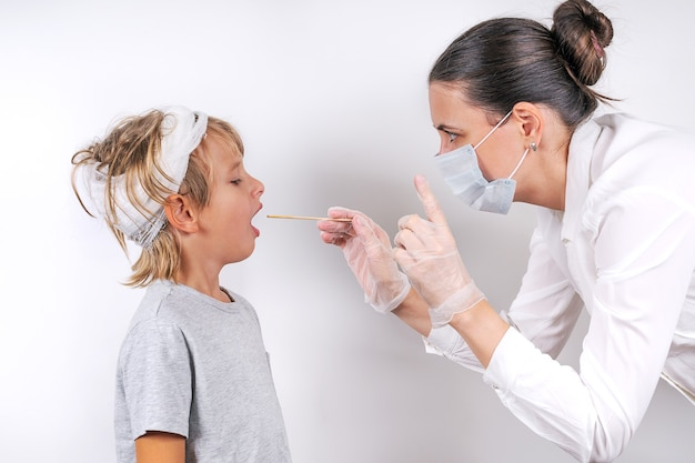 Concetto di medicina, assistenza sanitaria e pediatria. una dottoressa in maschera medica e guanti trasparenti esamina un ragazzino malato con trauma cranico. controlla la gola e fa un tampone per il coronavirus.