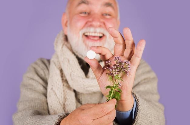 Erbe medicinali, sanità, prodotti farmaceutici e omeopatia, uomo con pillole e piante di erbe.