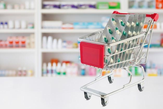 Capsula di confezione blister di pillole medicinali nel carrello sul bancone del negozio di farmacia con sfocatura scaffali della farmacia sfondo sfocato