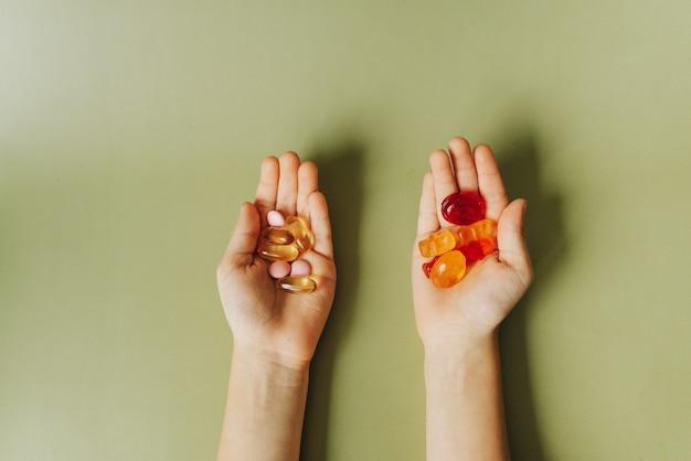 Pillole medicinali e caramelle nelle mani dei bambini