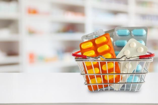 Il pacchetto delle pillole della medicina nel cestino della spesa con gli scaffali della farmacia della farmacia sfoca lo sfondo