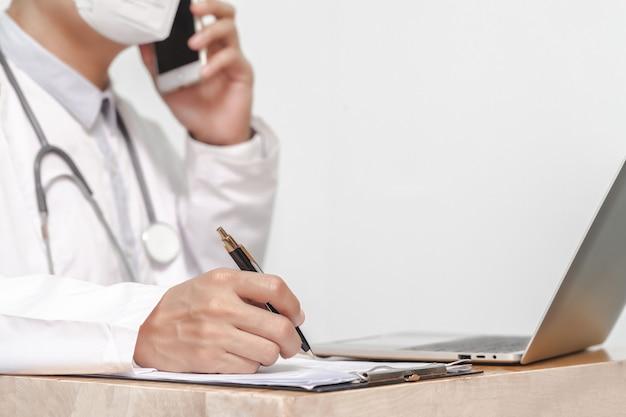 Concetto di medicina, professione, sanità e persone - chiuda in su del medico con appunti e stetoscopio