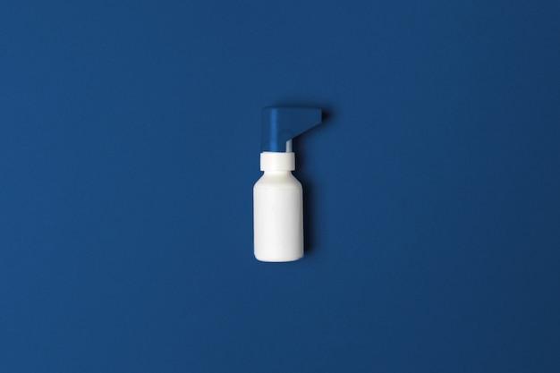 Fine della bottiglia dello spruzzo della medicina su su fondo blu classico